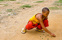 Young Monk playing marbles
