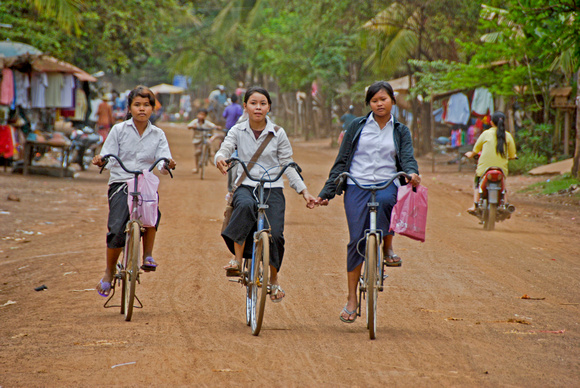 Three Girls on Bicycle in Village